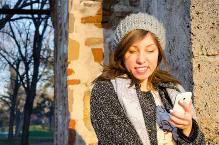 outoors: Smiling girl reading a message on her smartphone outdoors in a park Stock Photo