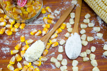 heap: Corn and flour in spoons on a wooden table