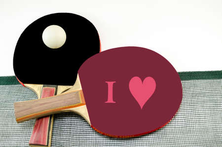 Two table tennis rackets one on top of the other and an old net isolated on white. One paddle is magenta and the other is black