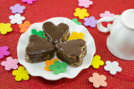 red tablecloth: Heart shaped chocolate cookies on a plate decorated with paper flowers on a red tablecloth Stock Photo