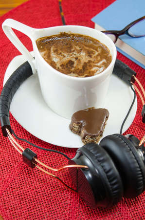 red tablecloth: Cup of coffee and headphones, book and glasses on a red tablecloth
