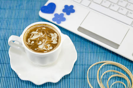 lap top: White cup of coffee with decorated foam and a white lap top on a blue tablecloth. Stock Photo