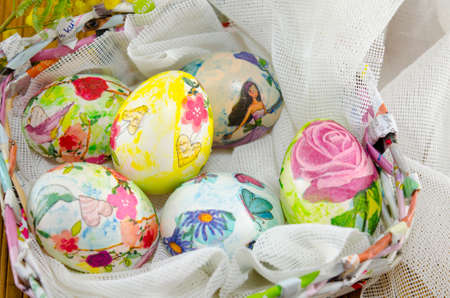 hand colored: Bunch of hand colored Easter eggs in a handmade paper egg basket Stock Photo