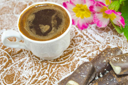 subtly: Cup of coffee with a subtly heartshaped foam decorated with flowers and banana shaped chocolate