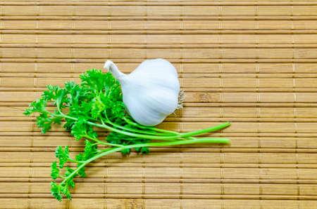 fresh garlic: Fresh garlic and parsley on a bamboo tablecloth shot above Stock Photo