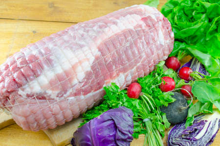 Raw meatloaf on a cutting board decorated with red radishes, lettuce and cabbage photo