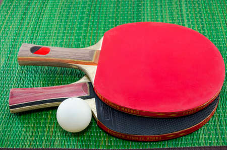 table surface: Two table tennis rackets and a ping pong ball on green surface Stock Photo