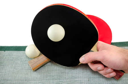 Male hand holding a ping pong racket and a table tennis ball above a net, isolated on white photo