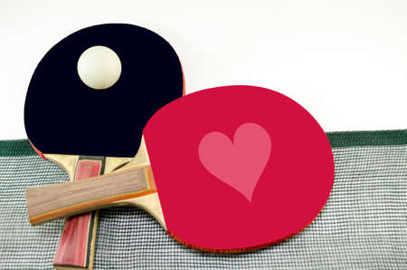 Two table tennis rackets one on top of the other and an old net isolated on white. One paddle is red and the other is black Stock Photo