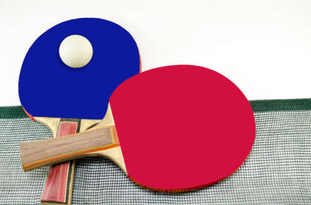 Two table tennis rackets one on top of the other and an old net isolated on white. One paddle is red and the other is black Reklamní fotografie - 38935095