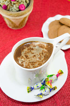 red tablecloth: Cup of coffee with bombons and biscuits on a red tablecloth Stock Photo