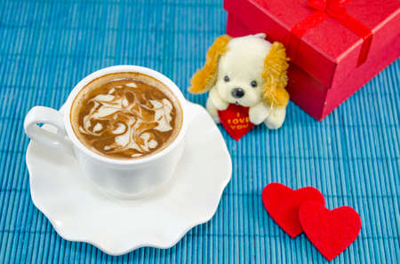 two hearts: Artisan coffee in a white cup with decorated foam.  Red present box for Valentines day, together with two hearts and a puppy doll.