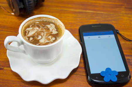 Cup of coffee with decorated foam and a smartphone on a wooden table with a headset in the background photo