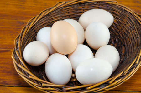 dozen: Dozen of white eggs in a wooden basket, placed on a table