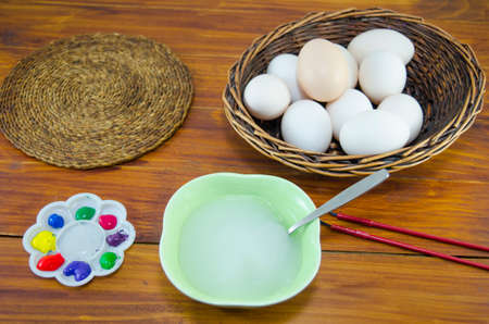 Cooked eggs ready to be painted for Easter, in a basket on a table photo