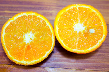 Two halves of  orange on a wooden table close up
