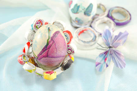 Handmade decoupage Easter egg on a handmade paper decorated with a paper butterfly photo