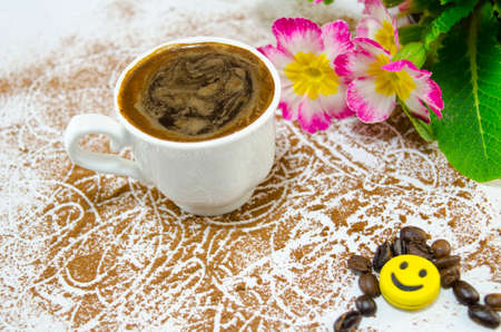 breakfast smiley face: Cup of coffee on a white table covered with grounded coffee. Decorated with flowers, coffee beans and a smiley face