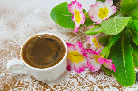 grounded: Cup of coffee on a white table covered with grounded coffee decorated with flowers Stock Photo