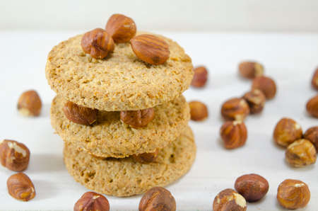 Integral biscuits on white table surrounded by hazelnuts