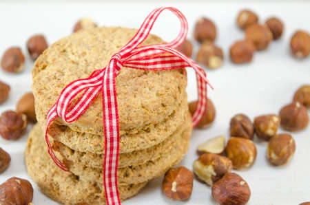 Integral biscuits on white table surrounded by hazelnuts photo