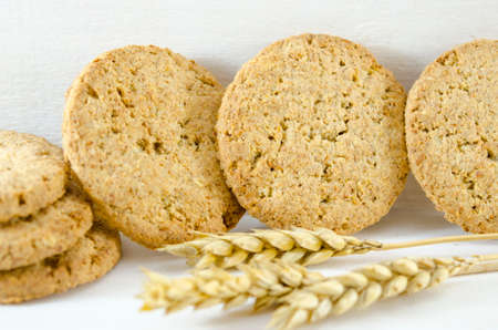 Fresh integral cookies and wheat on white background