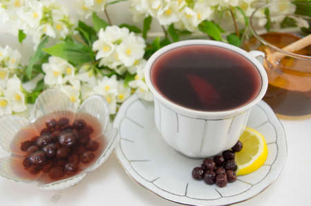 porcelain flower: Chokeberry tea in a porcelain cup on a flower decorated table Stock Photo