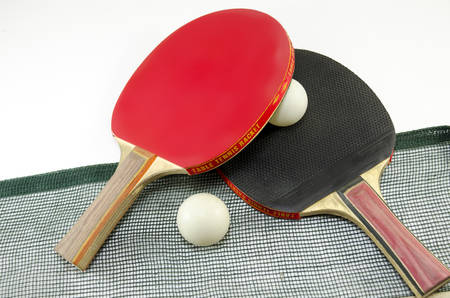 Two table tennis rackets one on top of the other and an old net isolated on white. One paddle is red and the other is black Reklamní fotografie