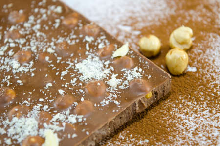 sprinkled: Hazelnut chocolate on a surface  sprinkled with cocoa and coconut powder Stock Photo