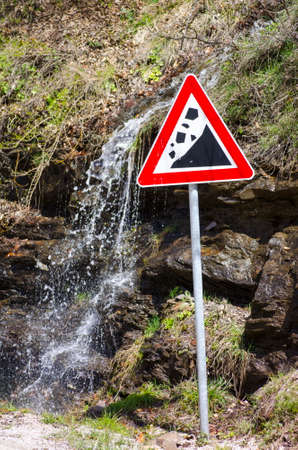 landslide: Small waterfall running behind a landslide sign outdoors