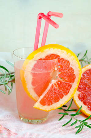 grapefruit juice: Fresh grapefruit juice in a glass decorated with red grapefruit slice on  a table decorated with rosemary branch Stock Photo