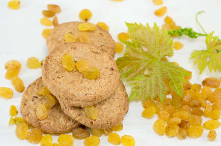 Integral cookies and yellow raisins with a large green flower on white