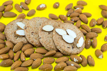Table covered with raw almonds and integral cookies Imagens