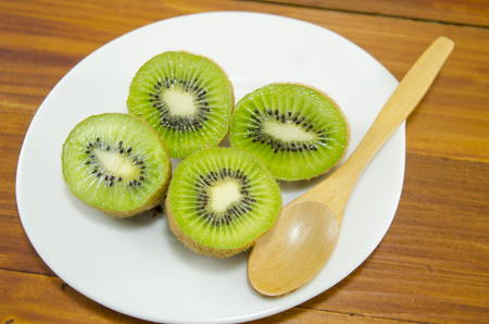 halved: Halved kiwis on a white plate with a wooden spoon