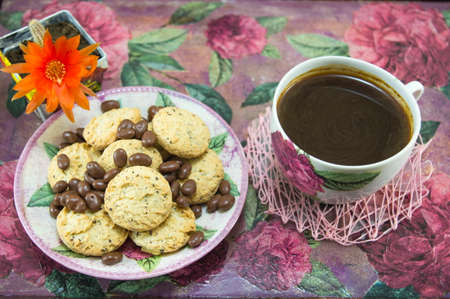 chocolate balls: Integral cookies and chocolate balls on a colorful coffe table with flowers Stock Photo