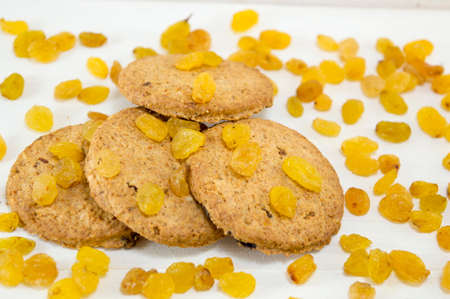 Integral cookies and yellow raisins on white