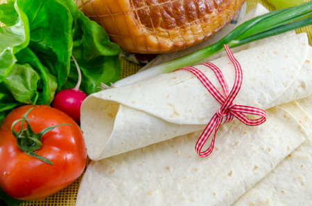 tortillas: Empty tortillas tied with a red ribbon on a table with tomato, lettuce and ham