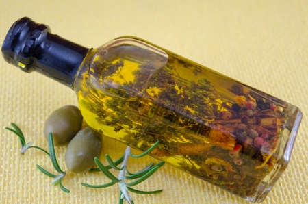 Olive oil bottle with herbs inside decorated with fresh green olives