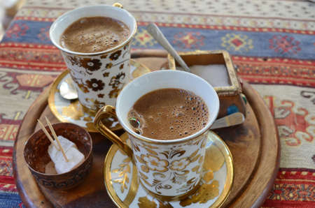 Two cups of Turkish coffee on wooden tray placed upon a colorful rug photo