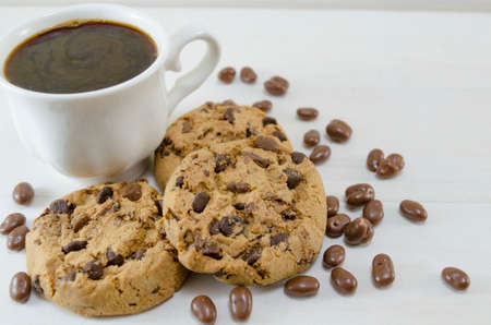 chocolate chip cookie: Chocolate chip cookies and a cup of coffee on white