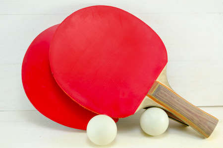 Two red table tennis rackets and balls on a wooden table photo
