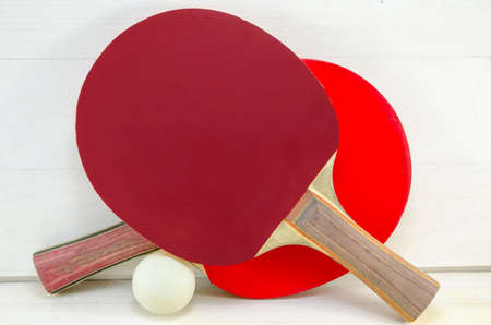 tabletennis: Two table tennis rackets and a ball on a wooden table Stock Photo