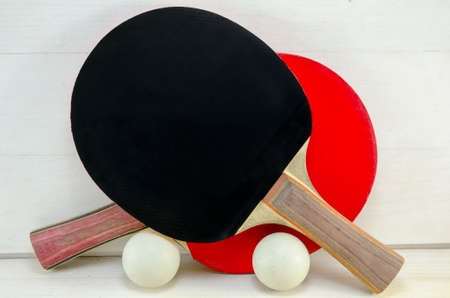 tabletennis: Two table tennis rackets and balls on a wooden table