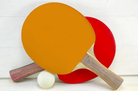 Two table tennis rackets and a ball on a wooden table Stock Photo