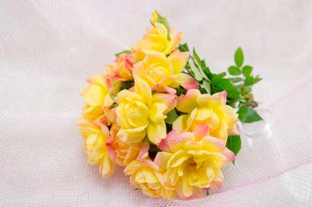 silken: Bouquet of yellow roses on a white silken sheet Stock Photo