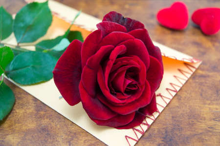 Rose and a handmade love letter on a table decorated with hearts