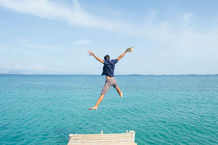 spread legs: Young man jumping from the dock into the sea with his clothes on