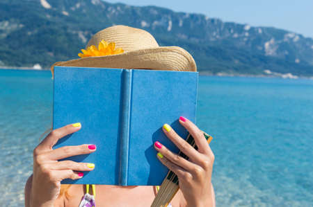 in the sand: Girl with straw hat reading book on the beach on a sunny day