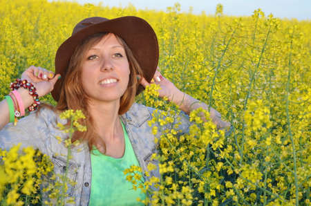 Beautiful girl posing with a hat in a field of yellow flowers photo