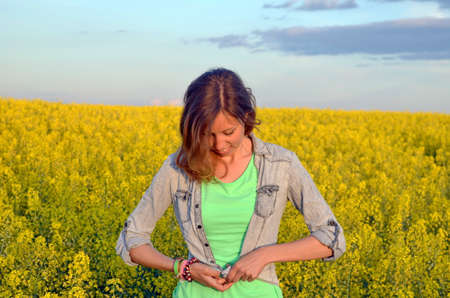 Brunette buttoning her denim shirt in a field of yellow flowers photo